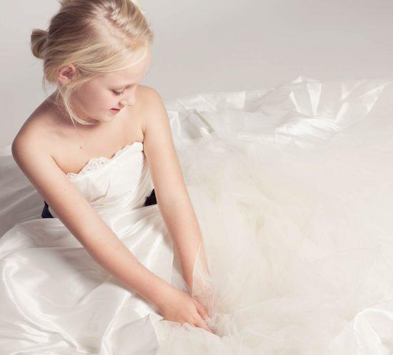 Fotoshoot van een klein meisje in moeders bruidsjurk
